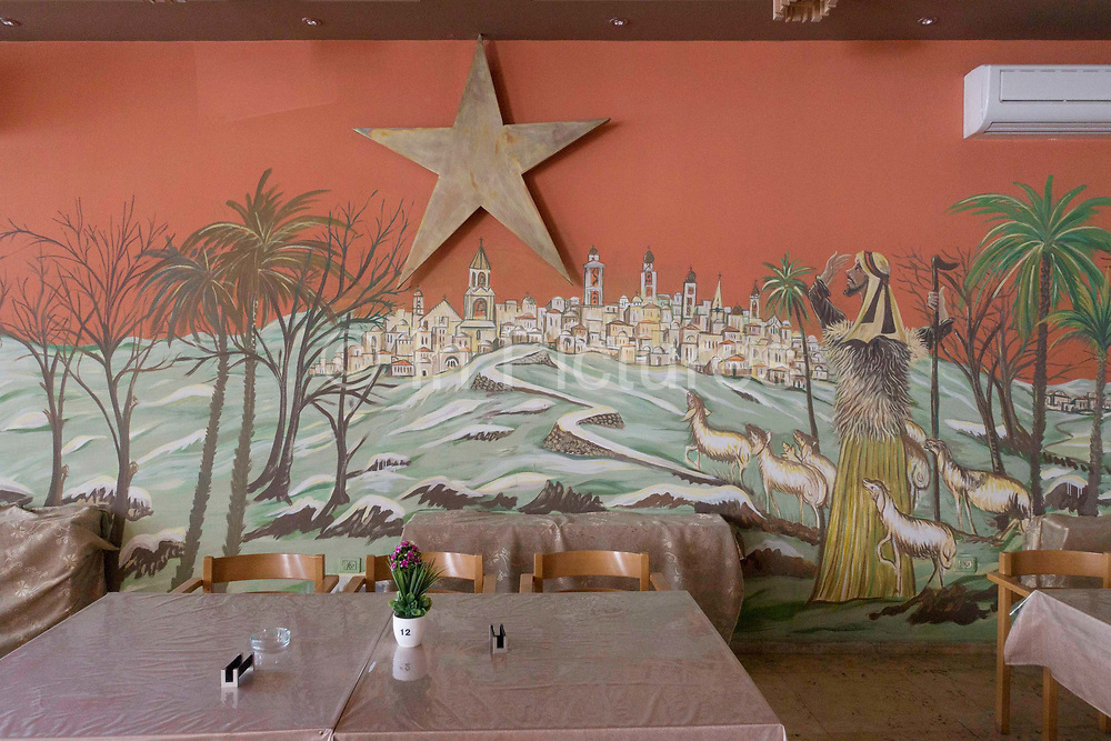A wall display showing the Christian Nativity in a restaurant on Bethlehem Square on 1st April 2016 in Bethlehem, West Bank. During the Palestine Marathon, thousands of runners, both professional and amateur come from across the globe to take part in the Right to Movement event.
