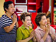 """22 AUGUST 2017 - BANGKOK, THAILAND: Women pray during a ceremony on the first day of Hungry Ghost Month at the Poh Teck Tung Shrine in Bangkok's Chinatown. The seventh lunar month (August - September) is when many Chinese believe Hell's gate will open to allow spirits to roam freely in the human world. Many households and temples hold prayer ceremonies throughout the month-long Hungry Ghost Festival (Phor Thor) to appease the spirits. During the festival, believers will also worship the Tai Su Yeah (King of Hades) in the form of paper effigies which will be """"sent back"""" to hell after the effigies are burnt.      PHOTO BY JACK KURTZ"""