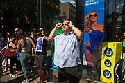 Summertime in London, England, UK. People out shopping in the busy West End area of Covent Garden, seen here hanging out near to Sunglasses Hut. A sign that summer is here. One man trying on some new shades.