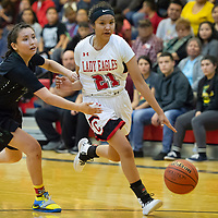Cassidy Begay (21) of Crownpoint tries to dribble away from Lashawna Brown (5) of Thoreau near the three point line at Crownpoint on Thursday. Crownpoint won 66-58.