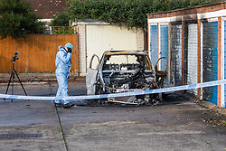 © Licensed to London News Pictures. 20/11/2019. London, UK. A police forensic officer examines a burnt out car near the crime scene at Owen Waters House in Fullwell Avenue, Ilford where a 19 year old man died after suffering stab injuries last night. Police were called at 22:20 on 19th November following reports of a fight outside Owen Waters House where they attended to a 19 year old man suffering from stab injuries, who died at the scene.  Photo credit: Vickie Flores/LNP