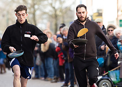 © Licensed to London News Pictures. 05/03/2019. Lichfield, Staffordshire, UK. The annual Shrove Tuesday pancake race taking place in Bore Street in the City Centre of Lichfield. Pictured, winner of the men's race, Glen Picknell, right. The event features races for men, women, children and those in fancy dress. The runners are supported by the voice of Town Crier Ken Knowles and the overall winner walks away with a brass and wooden Shrove Tuesday trophy. Photo credit: Dave Warren/LNP
