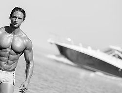 man walking out of the ocean near a speed boat