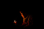 A girl's face is illuminated by the flame of a single candle inside a Nepalese guesthouse during an electrical power cut, Tadapani Guest House, Tadapani, Nepal