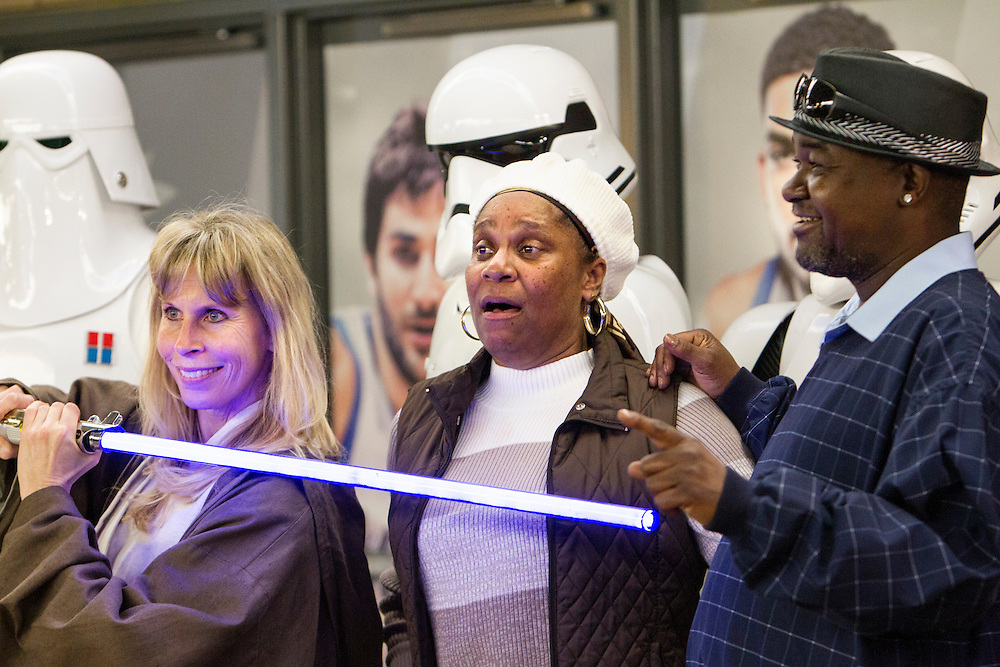 Joyce Brown, center, of Bloomington pretends to be afraid as her husband Stacy Brown holds his finger toward a lightsaber held by Jedi Jenny Braun of Hampton at Star Wars night at the Timberwolves game at Target Center in Minneapolis December 15, 2015.