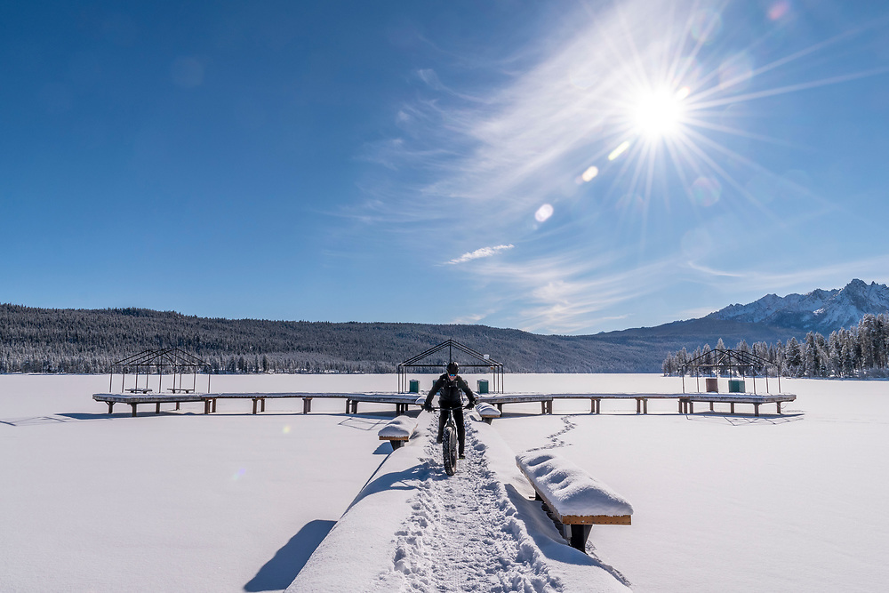 Snow Biking on the Redfish Lake Dock in winter with snow covered lake and pristine winter condition on a blue sky day in Central Idaho.  Licensing and Open Edition Prints.