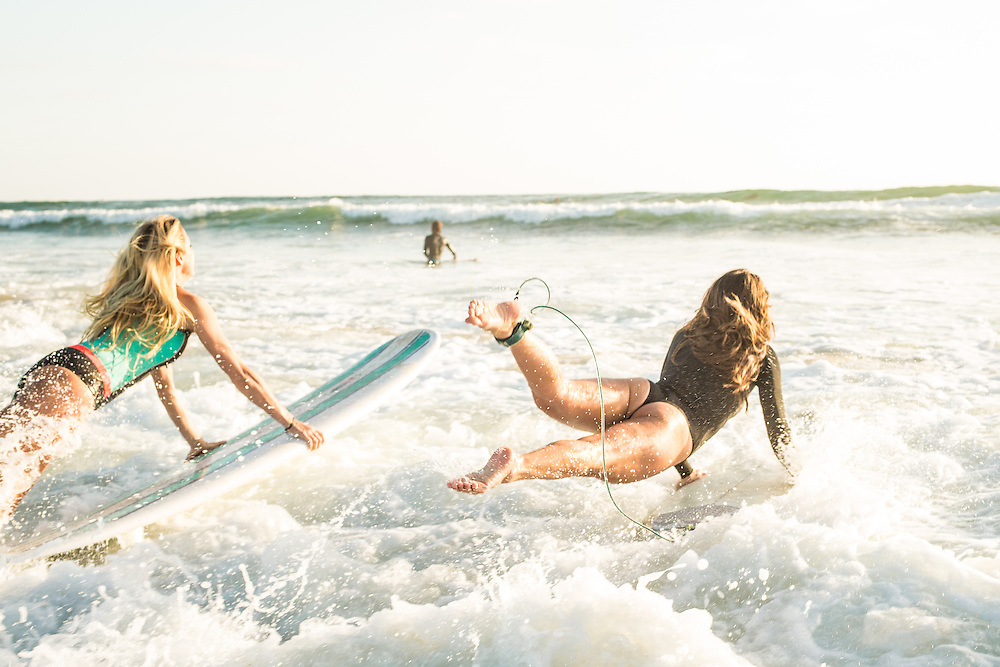 Two girl surfers jumping into the water with their boards and heading out surfing in San Diego, CA.