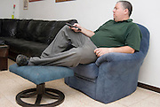 Overweight male in his 30s relaxing at home in front of the TV Model Release available