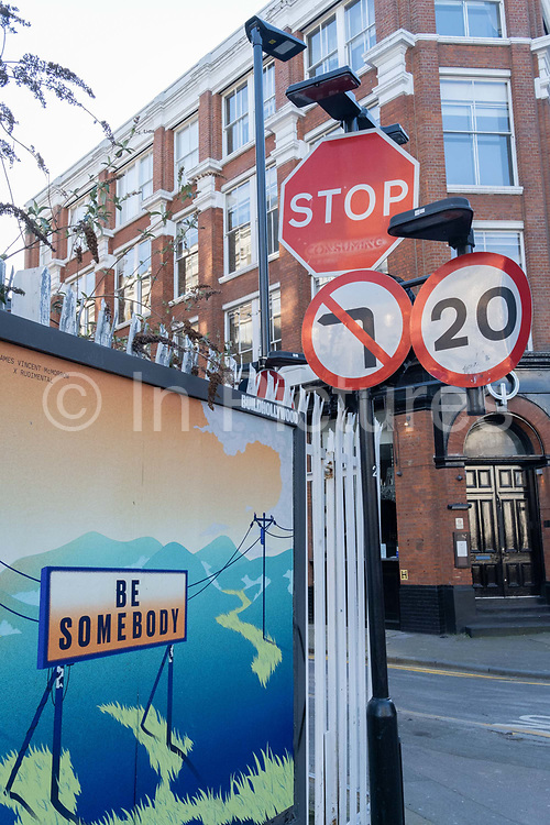 A billboard urging passers-by to Be Somebody is attached to railings in Shoreditch, on 26th February 2021, in London, England.