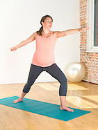 Pregnant woman (9 months) practices yoga on a mat.