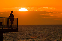 © Licensed to London News Pictures<br /> 17/06/2019 Aberystwyth UK<br /> After days of heavy rain and grey overcast skies, a fiery sunset over a woman standing on  the pier in Aberystwyth is a reminder of what 'flaming' June weather should be ;like<br /> <br /> photo credit: Keith Morris/LNP