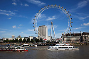 Tourists on cruise boats on the River Thames at Westminter, London. With the iconic London Eye behind this is one of the busiest areas for tourism in the city.