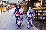 Japanese women in traditional kimono walks along the shops in the Nakamise dori shopping street in Asakusa, Tokyo, Japan.