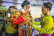 27 APRIL 2013 - BANGKOK, THAILAND: Performers in makeup get into their ornate costumes before a Chinese opera show in the Talat Noi neighborhood of Bangkok's Chinatown. Chinese opera was once very popular in Thailand and is usually performed in the Teochew language. Millions of Chinese emigrated to Thailand (then Siam) in the 18th and 19th centuries and brought their cultural practices with them. Recently its popularity has faded as people turn to performances of opera on DVD or movies. There are as many 30 Chinese opera troupes left in Bangkok. They travel from Chinese temple to Chinese temple performing on stages they put up in streets near the temple, sometimes sleeping on hammocks they sling under their stage. The opera troupes are paid by the temple, usually $700 to $1000 a night.   PHOTO BY JACK KURTZ