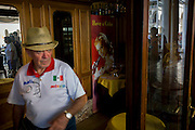 Tourist in cafe entrance inside the covered Procuratie Nuovo in Piazza San Marco, Venice, Italy.