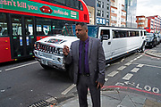 Asian man on Commercial Road in the East End looks down the street as a white stretch limousine Hummer passes containing a party of people in London, England, United Kingdom.