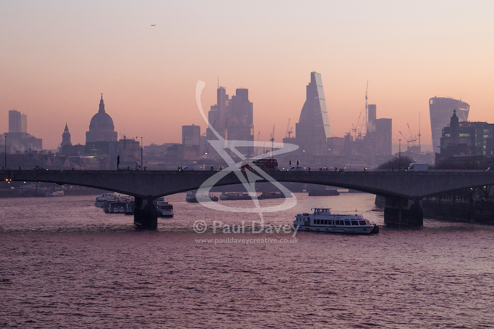 London, January 24th 2017. Photographed from Hungerford Bridge, the early morning light illuminates clouds and buildings of the city's skyline, with the predicted fog failing to appear. High pressure over the UK has caused pollution alerts as fumes are trapped beneath a cold layer of air.