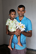 Father and son pose for a photograph before you pay homage to the Buddha with lotus flowers
