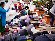 17 MARCH 2017 - KATHMANDU, NEPAL: A man sits and prays while others prostrate themselves during morning prayers at Boudhanath Stupa in Kathmandu. The stupa is the holiest site in Nepali Buddhism. It is also the center of the Tibetan exile community in Kathmandu. The Stupa was badly damaged in the 2015 earthquake but was one of the first buildings renovated.     PHOTO BY JACK KURTZ