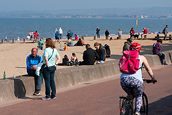 Portobello, Scotland, UK. 25 April 2020. Views of people outdoors on Saturday afternoon on the beach and promenade at Portobello, Edinburgh. Good weather has brought more people outdoors walking and cycling. The beach appears busy with possibly a breakdown in social distancing happening later in the afternoon. Promenade and beach appears busy but individual groups of people  generally maintaining social distancing.  Iain Masterton/Alamy Live News