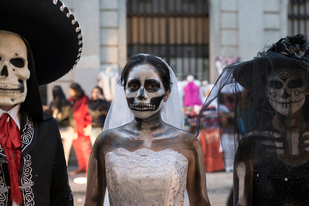 """People wearing costumes stand in a street in the Mexican city of Oaxaca during Day of the Dead celebrations (""""Día de los Muertos"""" in Spanish)."""