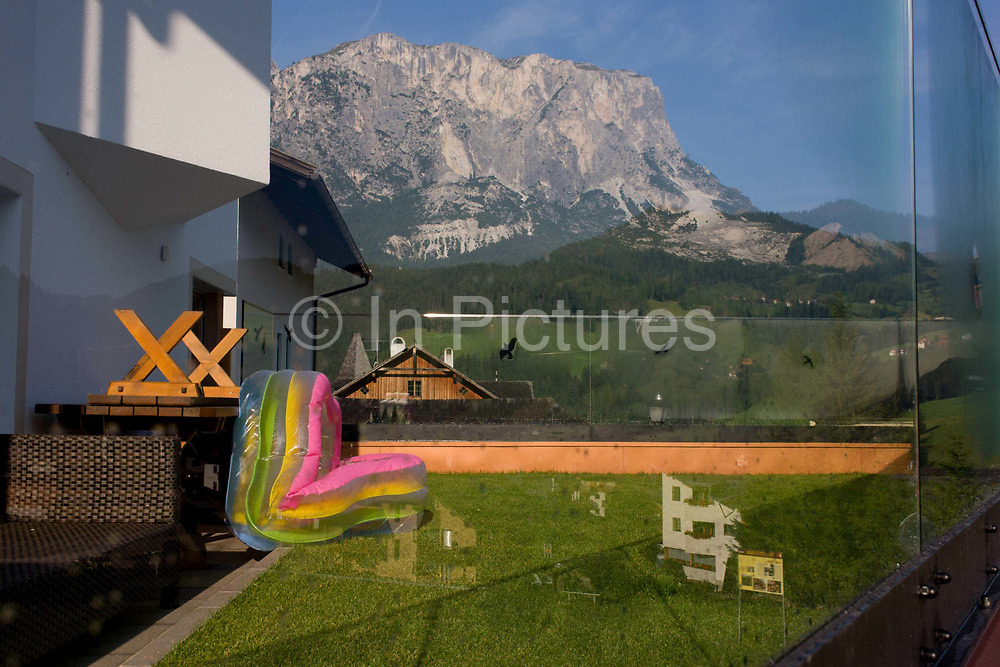 Back garden kindergarten toys in Leonhard-St Leonardo, a Dolomites village in the Badia region of south Tyrol, Italy. With the backdrop of a spectacular mountain peak we see the small patch of grass in a safe enclosure for children to play in. Life expectancy for south Tyroleans is 85 for females and 80 for males, higher than Italian national averages. According to the 2011 census, there are 505,000 inhabitants in south Tyrol.