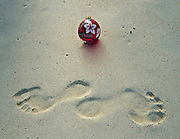 A Christmas ornament sits on a Hawaiian Beach with two footprints in the sand.