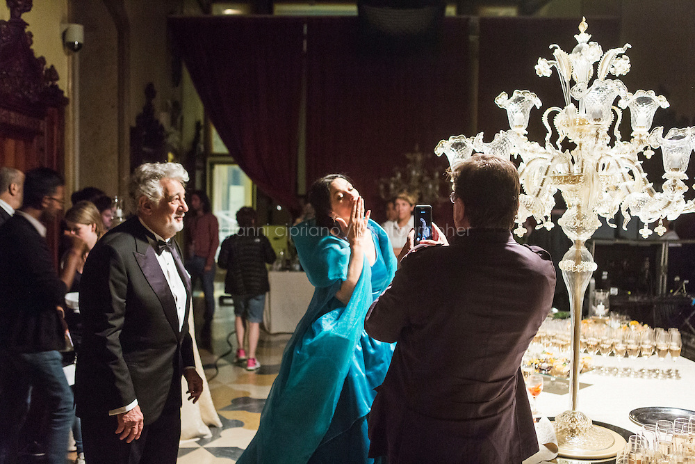 """VENICE, ITALY - 13 JULY 2016: Actress Monica Bellucci (50, center) send a video message to a fan during a beak in between scenes of the third season of """"Mozart in the Jungle"""", as conductor and tenor Placido Domingo (75, left) looks at her, at Palazzo Cavalli-Franchetti in Venice, Italy, on July 13th 2016.<br /> <br /> Mozart in the Jungle is an award-winning television series produced by Picrow for Amazon Studios. The pilot was written by Roman Coppola, Jason Schwartzman, and Alex Timbers and directed by Paul Weitz. The story was inspired by Mozart in the Jungle: Sex, Drugs, and Classical Music, oboist Blair Tindall's 2005 memoir of her professional career in New York."""