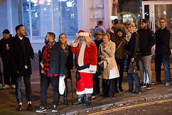 """© Licensed to London News Pictures. 19/12/2014. Brighton, UK. Santa Claus waits in the queue for a taxi  after going out on """"Mad Friday"""" night in Brighton East Sussex (19/12/2014). Across the UK thousands of people begin 2 weeks of festivities over the Christmas Period. Photo credit : Hugo Michiels/LNP"""