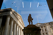 Days before the Chancellor Rishi Sunak delivers his Budget, Royal Exchage (left) and the Bank of England (right) are seen reflected in an office property's window along with the silhouetted statue of  civil engineer James Henry Greathead, on 1st March 2021, in London, England. James Henry Greathead (1844 – 1896), renowned for his work on the London Underground.