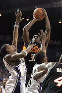 Oklahoma State forward David Monds (C) scores over Kansas State's Cartier Martin (L) in the first half at Bramlage Coliseum in Manhattan, Kansas, February 4, 2006.  The Cowboys and Wildcats are tied at halftime at 30-30.