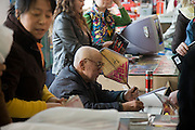 Mr Yang Peiyan, the farmer who found the Terracotta Warriors, signs books in the gift shop at Qin Museum, Xian