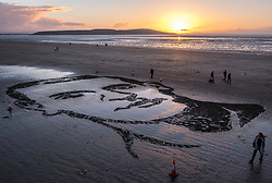"November 11, 2018 - Weston-Super-Mare, North Somerset, UK - Weston-super-Mare, North Somerset, UK. Pages of the Sea on the Armistice Day centenary, 1918-2018, of the end of the First World War. Pictured: a sand portrait of Lieutenant Colonel John Hay Maitland Hardyman, designed by sand artists Sand In Your Eye,  drawn into the sand on Weston's beach to be washed away as the tide comes in. Lieutenant Colonel John Hay Maitland Hardyman, D.S.O. M.C. (28 September 1894 – 24 August 1918) was born in Bath, was an Officer in the Royal Flying Corps and was awarded for gallantry. In May 1918, aged only 23, he became the youngest lieutenant colonel in the British Army. In December 1914, he was accepted for officer training with the Royal Flying Corps (forerunner of the RAF) at Brooklands, Surrey, though eventually served with the Somerset Light Infantry. He was awarded the Distinguished Service Order for conspicuous gallantry and devotion to duty. After the enemy had penetrated allied lines, John went forward through a heavy barrage to rally the troops and repel repeated enemy attacks over two days and three nights. He encouraged them through ""coolness and absolute disregard of personal danger"" to maintain a tactically important position. He was killed in action at Bienvillers, France, and buried in the military cemetery there. He was killed in France aged 24. Pages of the sea was devised by film-maker Danny Boyle and held at over 30 beaches across the UK on 11th November. Each event centres around a drawing of a large-scale portrait of a casualty from the First World War, designed by local sand artists, which will be washed away as the tide comes in. (Credit Image: © Simon Chapman/London News Pictures via ZUMA Wire)"