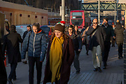 Commuters, including a woman in a Christmas pudding hat, walking through London on a winter morning. London, United Kingdom.