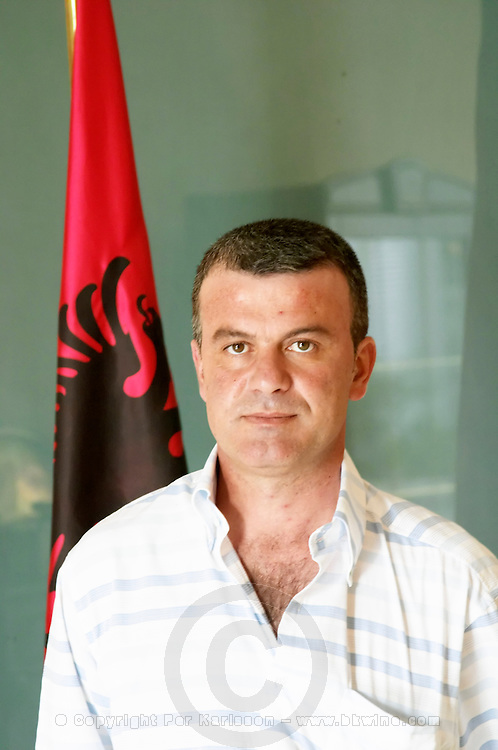 Mr Sokol Lumani the director and general manager posing in front of the Albanian flag and the flag of the winery. Kantina e Pijeve Gjergj Kastrioti Skenderbeu Skanderbeg winery, Durres. Albania, Balkan, Europe.