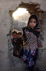 KABUL,AFGHANISTAN - SEPT. 11: Afghan children who recently returned from Pakistan look for water and materials to rebuild their home inside a destroyed neighborhood of  Kabul, Afghanistan September 11,2002.  (Photo by Ami Vitale/Getty Images)