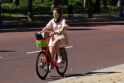 © Licensed to London News Pictures. 16/06/2021. London, UK. A woman cycles during sunny weather near St James's Park in Central London. Temperatures are expected to rise with highs of 30 degrees forecasted for parts of London and South East England today . Photo credit: George Cracknell Wright/LNP