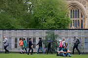 Lunchtime Londoners juxtaposed in front of a construction hoarding beneath the Palace of Westminster, UK's parliament gothic building currently undergoing extensive repairs and renovation. As a man sits on the grass, checking messages, other Londoners and visitors to the capital walk past. The arched window is at the base of Victoria Tower Park, beneath the Gothic architecture of Victoria architect Pugin's building, the seat of parliamentary government in the UK.