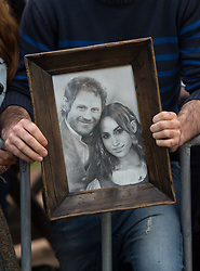 A man holds a sketch of the Duke and Duchess of Sussex as crowds wait for a walkabout in Rotorua on day four of the royal couple's tour of New Zealand.