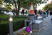 Man larking around with a traffic cone on his head. A visitor from out of town, playing around to make his grandchildren laugh. London, UK.