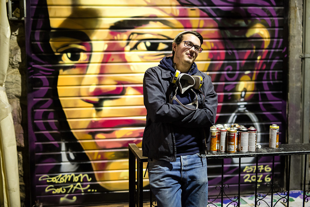 Artist Solomon Souza poses for a photograph in front of his latest street art piece depicting Israeli-Arab news anchor Lucy Aharish which he spray-painted over a closed shutter at the Mahane Yehuda Market, often called 'The Shuk' in Jerusalem, Israel, on February 24, 2016.