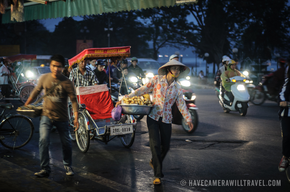 Busy night-time traffic on a street in Hanoi's Old Quarter.