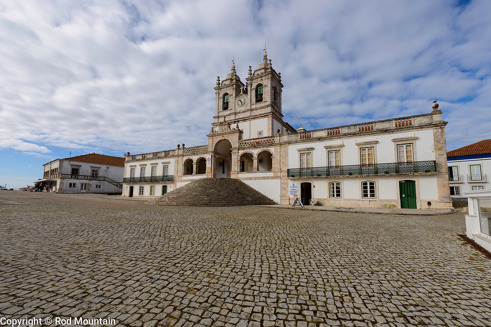 Nazaré, Portugal - February 12, 2018 - Santuário de Nossa Senhora da Nazaré (Sanctuary of Our Lady of Nazaré https://en.wikipedia.org/wiki/Sanctuary_of_Our_Lady_of_Nazaré ) is located on a hilltop near a popular tourist area that has incredible views of Nazaré and it's oceanside. The church was built in the 14th century.<br /> <br /> Image: © Rod Mountain<br /> <br /> http://www.rodmountain.com<br /> [l] <br /> <br /> Nikon D800 / Nikkor Lens<br /> @nikoncanada #NikonCA<br /> @NikonUSA #NikonNoFilter<br /> @nikoneurope #NikonEurope<br /> <br /> https://www.visitportugal.com/en<br /> @visitportugal <br /> <br /> https://en.wikipedia.org/wiki/Nazaré,_Portugal<br /> http://www.cm-nazare.pt/en<br /> @municipiodanazare @cmnazare @CMNazareMata <br /> <br /> #church #touristattraction #turismoemportugal #turismo #rotaportugal #ourladyofnazare<br /> #BBCTravel #nakedplanet #VirtuosoTravel #Fodorsonthego #TLPicks <br /> <br /> #artofvisuals #TravelAwesome #nakedplanet #CreativeExploreTakeOver#Travelingpost<br /> #bw_awards #bwmasters #bnwsouls #bnw_zone #awesomebnw #folkgood #traveldeeper #suitcasetravels #photooftheday #instatraveling