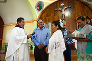 In this July 23, 2016 photo, Francisca Santiago, 65, and her lifelong partner Pablo Ibarra, 75, crack a smile as they exchange wedding vows at the church in Santa Ana, in the Mexican state of Oaxaca. The Rev. Domingo Garcia Martinez performed Ibarra and Santiago's wedding in front of about 250 family and friends. NICK WAGNER / ASSOCIATED PRESS