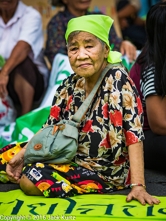 03 OCTOBER 2016 - BANGKOK, THAILAND:  A woman sits on the street in front of the UN headquarters in Bangkok during a World Habitat Day protest. In 1985, the UN General Assembly declared that World Habitat Day would be observed on the first Monday of October every year.  The declaration noted that every person deserves a decent place to live. In Bangkok this year, hundreds of people marched to the United Nations' offices to deliver a letter addressed to the UN Secretary General noting that forced evictions to facilitate urban renewal and gentrification was resulting in an increase in homelessness and substandard housing. Protesters and housing rights' activists also marched to the Prime Minister's Office and Bangkok city hall to express their concerns.     PHOTO BY JACK KURTZ
