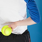 A woman in a blue and white baseball jersey holds a softball behind her back, preparing to throw it. Photographed with studio lights in front of a blue backdrop.