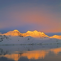 The sun rises over Anvers Island and the Neumeyer Channel, near the Antarctic Peninsula.