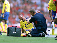 Fredrik Ljungberg (Arsenal) feels the pain as Gary Lewin (trainer) checks out his shoulder injury. Manchester United v Arsenal. Community Shield.10/8/03. Millennium Stadium. Credit : Colorsport/Andrew Cowie.