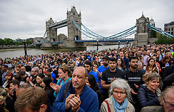 © Licensed to London News Pictures. 05/06/2017. London, UK. Members of the public gather in front of Tower Bridge for vigil at Potters Fields Park outside City Hall in London for those who lost their lives in the London Bridge terror attack. Three men attacked members of the public  after a white van rammed pedestrians on London Bridge. Ten people including the three suspected attackers were killed and 48 injured in the attack. Photo credit: Ben Cawthra/LNP