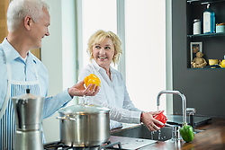 Mature couple cooking and washing pepper, smiling